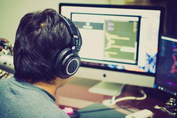Jongen achter computer met koptelefoon